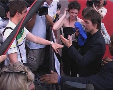 Hollywood star Tom Cruise wipes his face with a towel, Sunday June 19, 2005, in central London after being doused with water during his walkabout before the premiere of his new film War of the Worlds. Cruise was speaking to journalists when a man with a microphone squirted water in his face and all over his jacket.